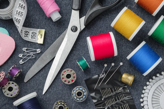 Sewing items: tailoring scissors, measuring tape, thimble, spools of thread, including pins, needles and sewing accessories on sewing cloth. View from above.