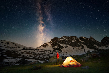 Hiker standing near tent and looking at the milky way in mountains at night