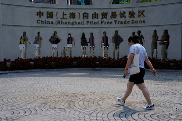 A woman walks at the entrance of the Shanghai Free Trade Zone in Pudong district, in Shanghai