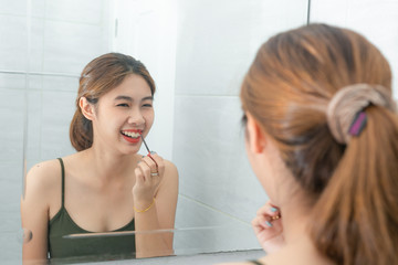 Asian women happiness makeup by red lipstick with mirror in bathroom.