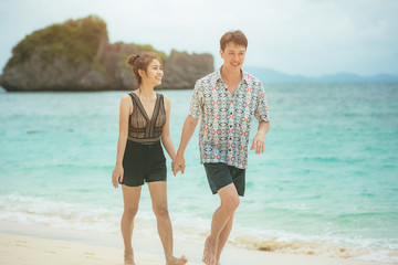 Beach couple lover walking on the beach honeymoon vacation summer holidays romance.