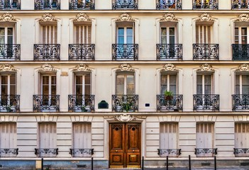 Street view of the elegant facade of an old Parisian apartment building. Vintage style photo. Wall mural