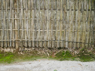 old bamboo wall , old wooden fence and grass