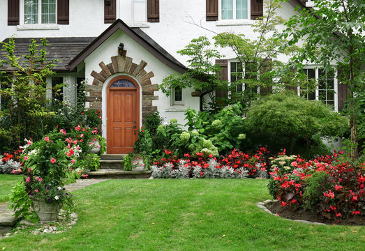 stucco house with wooden front door and flowers in front yard