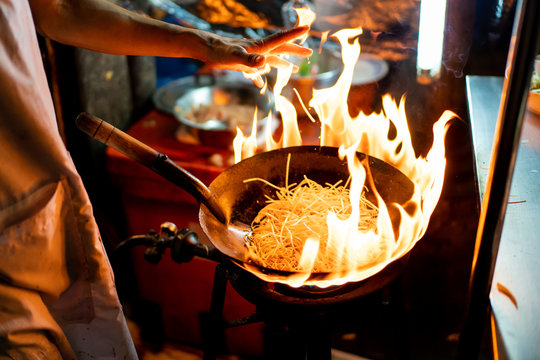 Street food chef cooking fry noodle in a black pan with fire exposure.  The traditional Thai and Chinese food in China Town in Bangkok, Thailand.
