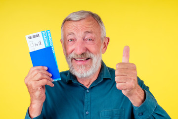 smiling senior man holding passport in blue cover and tickets studio yellow background