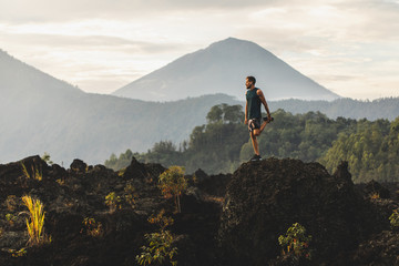 Man doing stretching and preparing for workout and running outdoors. Amazing mountain view on background. Adventure sports concept. Wall mural