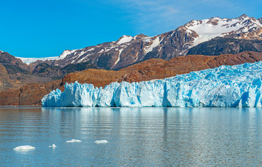 The majestic Grey Glacier in summer with small icebergs in Lago Grey with the Andes mountain range in the background, Torres del Paine national park, Puerto Natales, Patagonia, Chile.