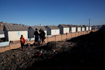 Children play next to houses belonging to the Akamasoa community, near the Andralanitra garbage dump in Antananarivo