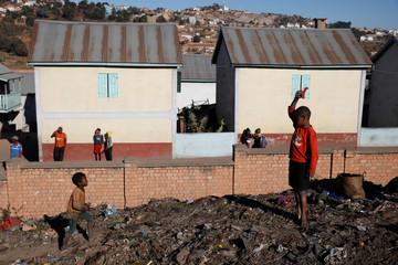 Children play next to houses belonging to the Akamasoa community near the Andralanitra garbage dump in Antananarivo