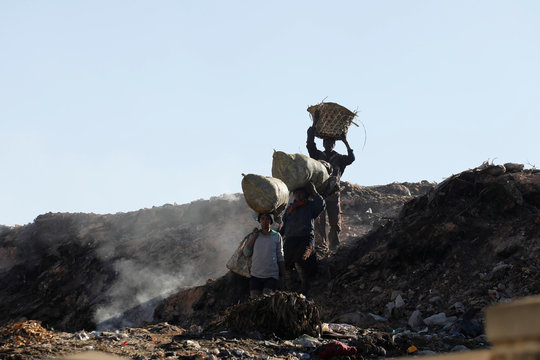People carry sacks with items they collected in the Andralanitra garbage dump in Antananarivo