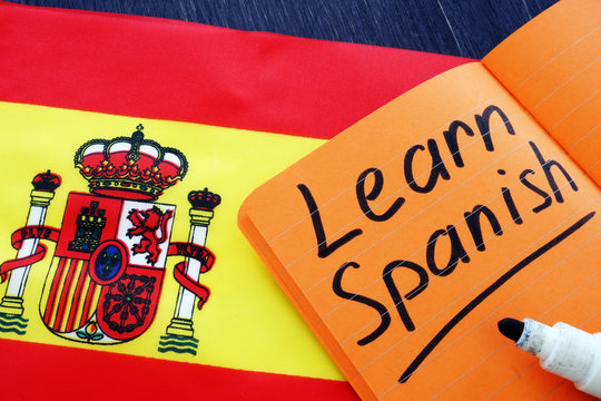 Learn Spanish written in the notebook with flag.
