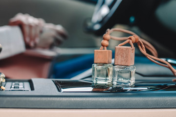 Two small glass bottles with car perfume on car panel. Female driver on blurry background.