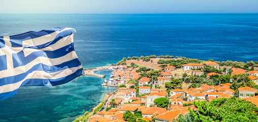 Fotomurales - Greece National Flag on top of the castle of Molyvos. Aerial view of Mithymna town.