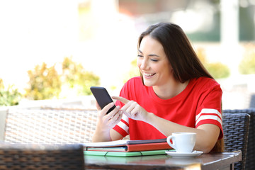 Happy student in red browsing phone content in a bar
