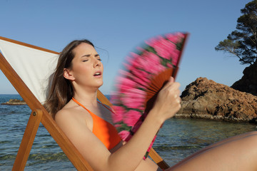 Unhappy sunbather suffering heat stroke on the beach