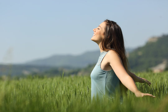 Happy woman breathing fresh air and touching wheat