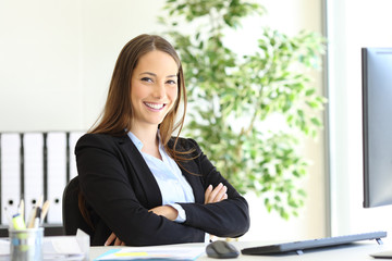 Happy businesswoman at office posing looking at you