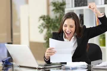 Excited businesswoman reading good news in letter