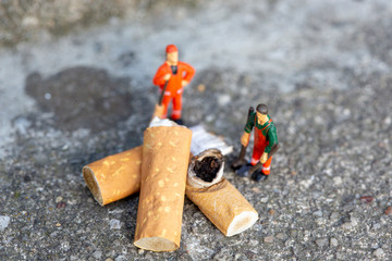 Two miniature garbage men cleaning and sweeping smoked cigarettes on the street which pollute the enviroment
