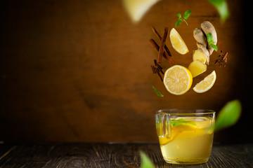 Flying ginger tea ingredients - lemon, cinnamon, mint, rustic background