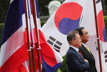 South Korean President Moon Jae-in and Thailand's PM Prayuth Chan-ocha listen to their national anthems during a welcoming ceremony at the government house in Bangkok