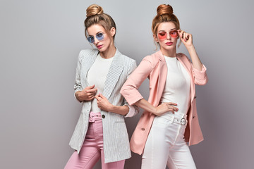 Fashion. Two Beautiful woman in autumn stylish jacket, make up. Lovable sisters friends. Sensual glamour well dressed girl, trendy hair.Creative fashionable portrait, beauty makeup autumnal concept
