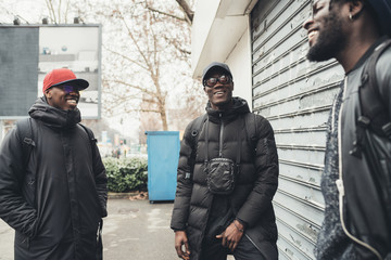 three african men standing in the street and having conversation