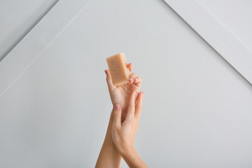 Female hands with soap bar on light background