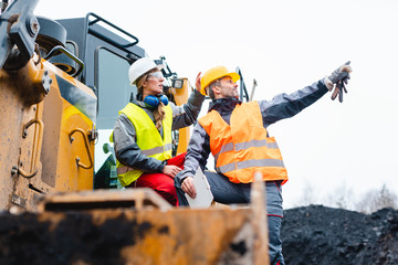 Man and woman as workers on excavator in quarry