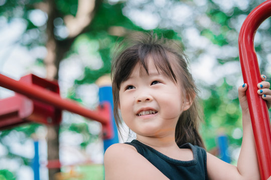 Happy asian little girl playing in playground