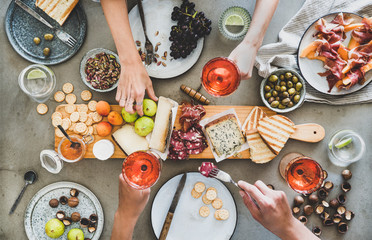 Mid-summer picnic with wine and snacks. Flat-lay of charcuterie and cheese board, rose wine, nuts,...