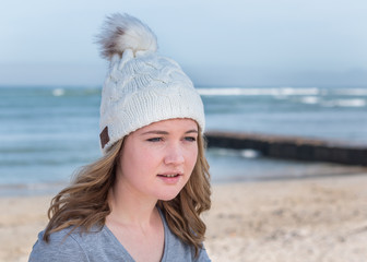 Female model wearing white knitted beanie with Bluetooth speakers inside, listening to music outdoors.