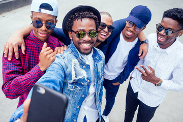 a group of five fashionable cool African American guys students communicating on the street looking at smartphone take pictures selfie on phone in street