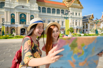 tourist women in exciting discuss find location in map guide information to visit the palace temple in Bangkok of Thailand, Emerald Buddha Temple, Wat Phra Kaew, the Royal Palace popular tourist place