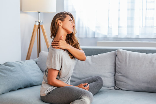 Pain in the shoulder. Upper arm pain, People with body-muscles problem, Healthcare And Medicine concept. Attractive woman sitting on the bed and holding painful shoulder with another hand.