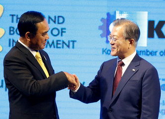Thailand's Prime Minister Prayuth Chan-ocha and South Korean President Moon Jae-in shake hands as they attend Thailand-Korea Business forum in Bangkok