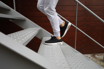 Detail of sporty woman running shoes while she is training climbing stairs. Urban fitness outdoor...