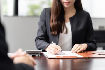 税の相談を受け、計算をする女性税理士 Fototapete