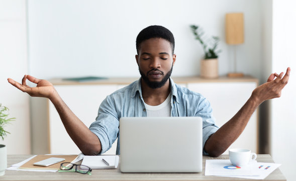 Relaxed african american businessman meditating at office