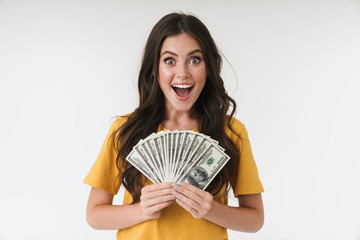 Young girl isolated over white wall background holding money.