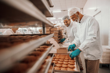 Two hardworking dedicated Caucasian employees dressed in white sterile uniforms collecting and packing cookies in boxes. Food plant interior. Wall mural