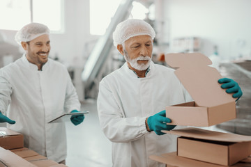 Caucasian working senior in white uniform putting and preparing boxes while smiling supervisor holding tablet and watching him. Food plant interior.