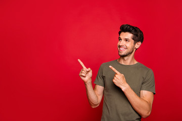 Photo of macho guy indicating fingers on low shopping spices wear grey t-shirt isolated on red background