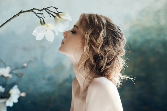 Perfect bride, portrait of a girl in a long white dress. Beautiful hair and clean delicate skin. Wedding hairstyle blonde woman. Girl with a white flower in her hands