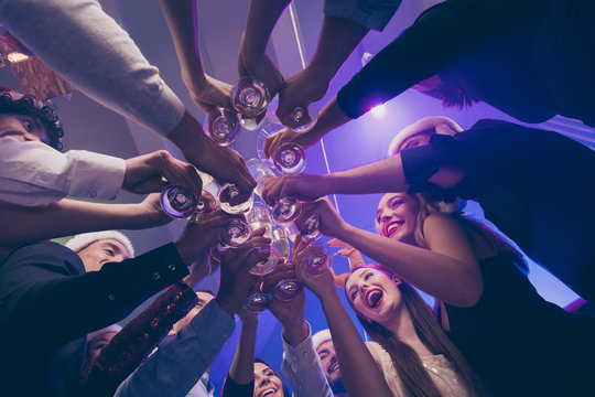 Low below angle view of nice attractive cheerful cheery girls and guys having fun rest relax clinking wineglass congrats corporate event feast celebratory in luxury place nightclub lights indoors