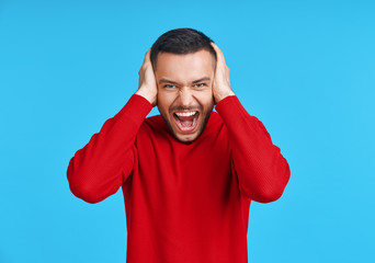 Stressed emotional young man screaming and closing ears by his hands isolated on blue background