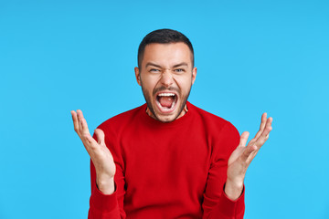 Screaming angry man on blue background