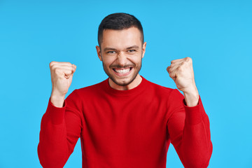 Happy man celebrating his success with winner gesture on blue background