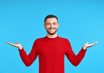 Handsome happy man presenting copy space isolated on blue background